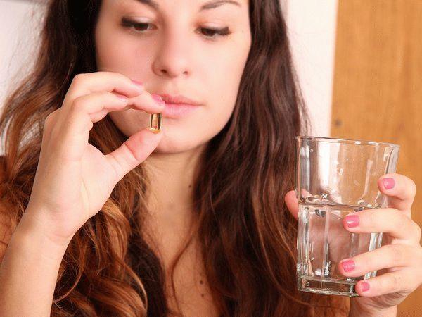 женщина смотрит на таблетку