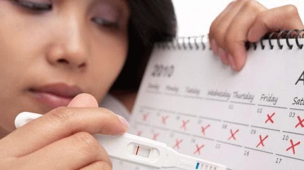 женщина с календарем и тестом на беременность