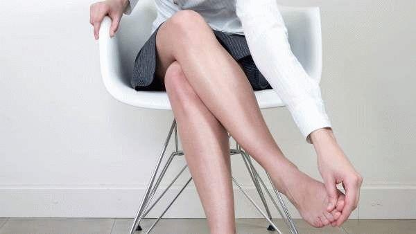 женщина держится за ноги