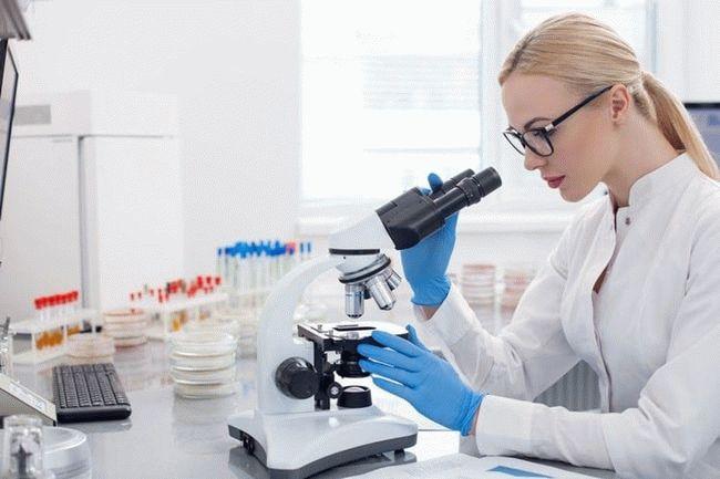 девушка смотрит в микроскоп