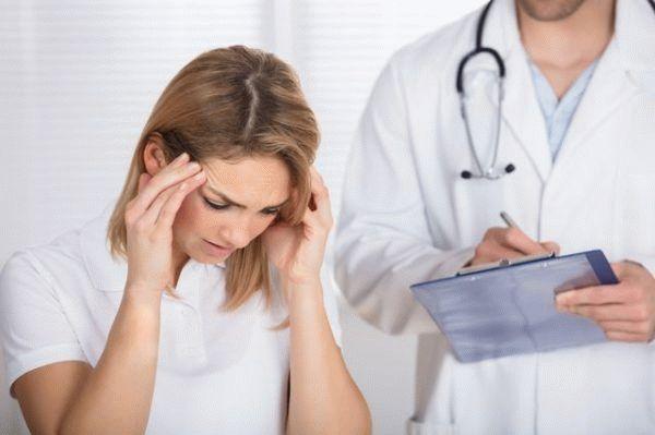 девушка жалуется врачу на головную боль